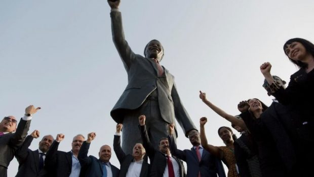 Palestinians pose for a memorial picture with a sculpture of the first democratically elected South African president and anti apartheid leader Nelson Mandela, in the West Bank city of Ramallah, Tuesday, April 26, 2016. Palestinians honored Mandela unveiling his statue on a square in Ramallah, on South Africa's Freedom Day that is observed annually to commemorate the first post apartheid elections held on April 27, 1994. (AP Photo/Nasser Nasser) (The Associated Press)