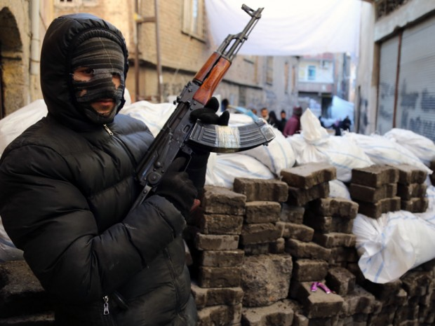 A PKK militant stands at a barricade as some of thousands of people flee from the historic Sur district of the mainly-Kurdish city of Diyarbakir, Turkey.(AP Photo/Murat Bay)