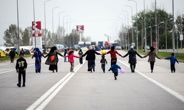 Migrants hold hands as they block the highway near the town of Polykastro in northern Greece in protest at the closure of the border with Macedonia. Photograph: Bulent Kilic/AFP/Getty Images