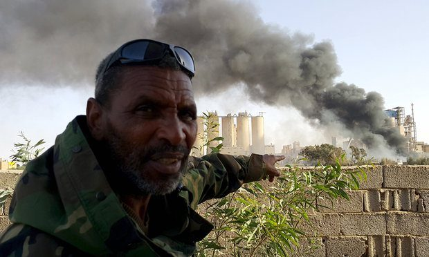 A fighter loyal to the eastern regime outside a Benghazi factory set ablaze in clashes on Friday. The civil war is raging amid efforts to form a single government. Photograph: Reuters