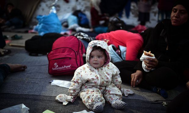 A baby sits on a blanket near his mother in the town of Chios, where refugees who managed to leave the Vial detention centre camp out. Photograph: Louisa Gouliamaki/AFP/Getty Images