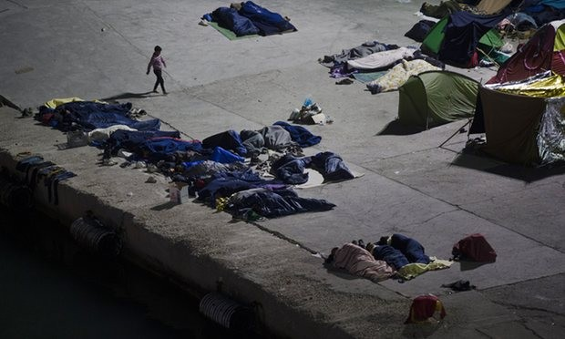 People sleep at the port on Chios island, Greece. Photograph: Petros Giannakouris/AP