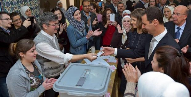 Syria's President Bashar al-Assad his receives his identification card next to his wife Asma (to his right), after casting their votes, inside a polling station during parliamentary elections in Damascus, Syria in this handout picture provided by SANA on April 13, 2016. REUTERS/SANA/Handout via Reuters