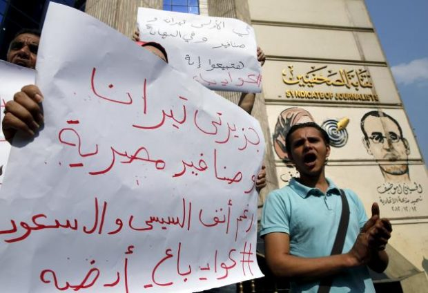 """Egyptian activists shout anti-President Abdel Fattah al-Sisi and government slogans during a demonstration protesting against the government's decision to transfer two Red Sea islands to Saudi Arabia, in front of the Press Syndicate in Cairo, Egypt, April 13, 2016. The sign reads, """"The two Islands Tiran and Sanafir are the Egyptians"""". REUTERS/Amr Abdallah Dalsh"""