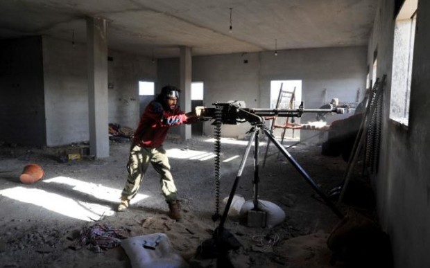 Fighters against the Islamic State group fire weapons in the Hawari area, south-west of the city of Benghazi, Libya CREDIT: MOHAMMED EL-SHAIKY/AP PHOTO