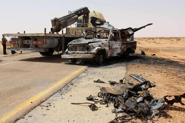 Carnage: A truck removes the remains of a burnt-out vehicle following a car bomb attack on a security post in the Saddada area