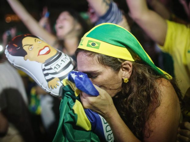 A pro-impeachment supporter kisses a Brazilian flag, as lower house deputies vote to approve the motion to continue the impeachment process of President Dilma Rousseff Getty Images