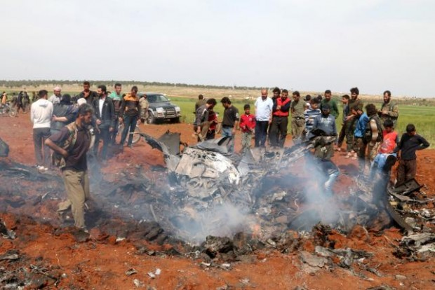 Rebel fighters and civilians gather around the wreckage of a Syrian warplane that was shot down in the Talat al-Iss area, south of Aleppo, Syria April 5, 2016. REUTERS/AMMAR ABDULLAH