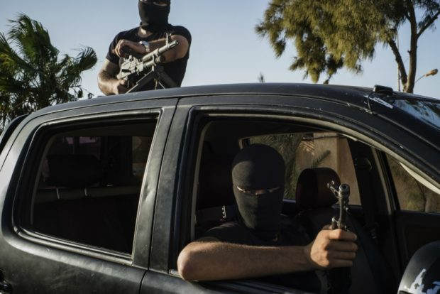Members of the Black Masks are seen in the city of Zuwara, Libya. The volunteer milita rides through town in pickups with tinted windows, combating everything from burglars to militant groups from outside the city. LORENZO TUGNOLI FOR THE WASHINGTON POST