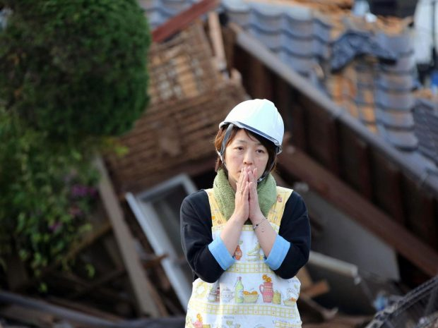 A resident stands in front of a damaged house in Mashiki, Kumamoto prefecture, southern Japan. The region has been hit by two powerful earthquakes in as many days. Kyodo News/AP
