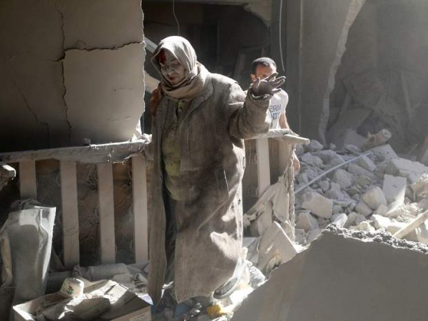A woman emerges from the rubble of a building after the attack
