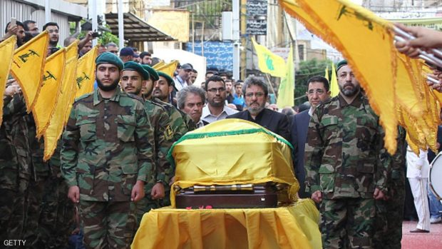 Adnan (C-L) and Hassan Badreddine (C-R), brothers of slain top Hezbollah commander Mustafa Badreddine who was killed in an attack in Syria, mourn next to his casket during the funeral  in the Ghobeiry neighbourhood of southern Beirut on May 13, 2016. Hezbollah announced that Badreddine had been killed in an attack in Syria where the Shiite militant group has deployed thousands of fighters in support of the Damascus regime. The group said it was still investigating the cause of the blast near Damascus airport but it did not immediately point the finger at Israel as it did when the commander's predecessor was assassinated in the Syrian capital in 2008. / AFP / ANWAR AMRO