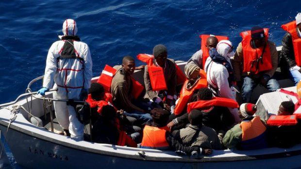 Migrants sit on a rescue boat during a rescue operation of migrants by Italian Navy vessels in this March 18, 2016 handout picture provided by Marina Militare. REUTERS/Marina Militare/Handout via Reuters