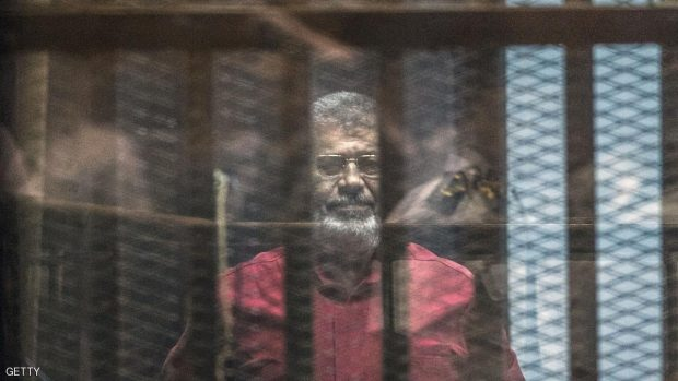 Egypt's ousted Islamist president Mohamed Morsi, wearing a red uniform, stands behind the bars during his trial in Cairo at the police academy in Cairo on April 23, 2016. KHALED DESOUKI/AFP/Getty Images