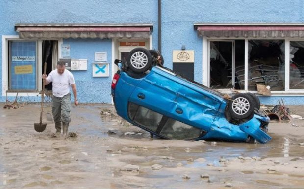 A man walks past a smashed car lying on its roof CREDIT: GETTY
