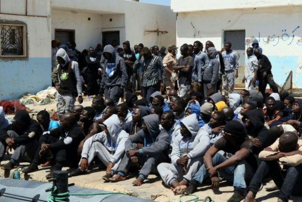 Illegal migrants sit on the dock at the Tripoli port after 117 migrants of African origins, including six pregnant women, were rescued by two coast guard boats off the coast of Libya on June 7, 2016 ©Mahmud Turkia (AFP)