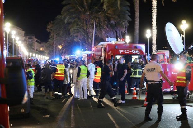 """Police officers, firefighters and rescue workers are seen at the site of an attack on July 15, 2016, after a truck drove into a crowd watching a fireworks display in the French Riviera town of Nice. A truck ploughed into a crowd in the French resort of Nice on July 14, leaving at least 60 dead and scores injured in an """"attack"""" after a Bastille Day fireworks display, prosecutors said on July 15.  / AFP PHOTO / Valery HACHE"""