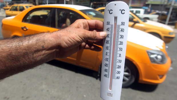 An Iraqi man shows a thermometer reading more than fifty degrees Celsius on July 30, 2015 in the capital Baghdad. AFP PHOTO / AHMAD AL-RUBAYE (Photo credit should read AHMAD AL-RUBAYE/AFP/Getty Images)