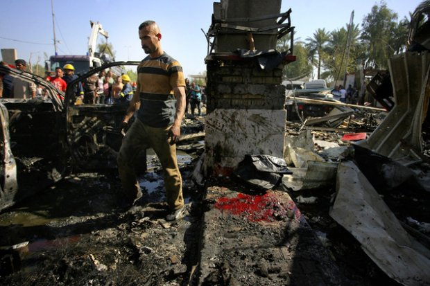 Civilians and security forces gather at the scene of a suicide bomb attack in Hillah, about 60 miles (95 kilometers) south of Baghdad, Iraq, Sunday, March 6, 2016. A suicide bomber on Sunday rammed his explosives-laden fuel truck into a security checkpoint south of Baghdad, killing and wounding dozens, officials said, the latest episode in an uptick in violence in the war-ravaged country. (AP Photo/Anmar Khalil)