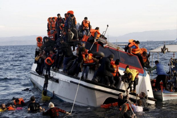 Refugees, most of them Syrians, struggle to leave a half-sunken catamaran carrying around 150 refugees as it arrives on the Greek island of Lesbos