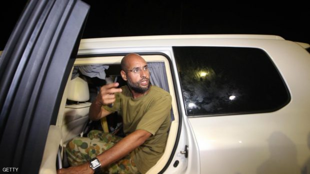 """Saif al-Islam Kadhafi, son of Libyan leader Moamer Kadhafi, appears in front of supporters and journalists at his father's residential complex in the Libyan capital Tripoli in the early hours of August 23, 2011. Seif al-Islam, wanted by the International Criminal Court for crimes against humanity and who ICC prosecutor Luis Moreno-Ocampo earlier said had been arrested by the rebels, claimed the insurgents had suffered """"heavy casualties"""" when they stormed Kadhafi's Bab al-Azizya compound in Tripoli. AFP PHOTO/IMED LAMLOUM (Photo credit should read IMED LAMLOUM/AFP/Getty Images)"""