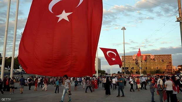 People shout, gestures and hold Turkish national flags as they gather in Taksim square in Istanbul, on July 18, 2016 following the military failed coup attempt of July 15. Turkish security forces on July 18 carried out new raids against suspected plotters of the botched coup against the rule of President Recep Tayyip Erdogan, as international concern grew over the scale of the crackdown. Thousands of pro-Erdogan supporters waving Turkish flags filled the main Kizilay Square in Ankara while similar scenes were seen in Taksim Square in Istanbul, AFP photographers said. / AFP / DANIEL MIHAILESCU        (Photo credit should read DANIEL MIHAILESCU/AFP/Getty Images)