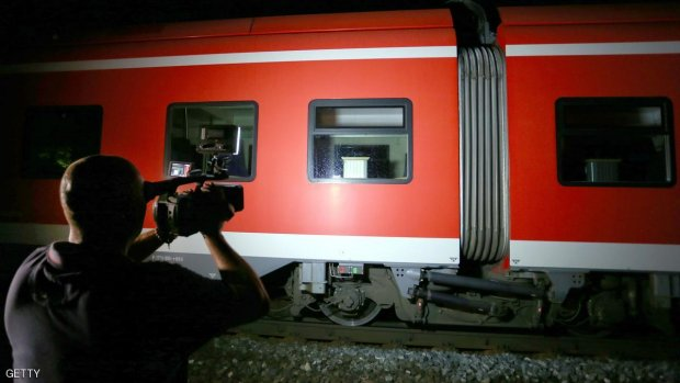 A cameraman films a regional train in Wuerzburg southern Germany on July 18, 2016 after a man attacked train passengers with an axe.  German police killed the man after he attacked passengers on a train with an axe and a knife, seriously wounding three people, news agency DPA reported citing police.  / AFP / dpa / Karl-Josef Hildenbrand / Germany OUT        (Photo credit should read KARL-JOSEF HILDENBRAND/AFP/Getty Images)