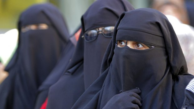 """Egyptian women wearing """"Niqab"""" line up outside a polling station to vote in the second round of a referendum on a disputed constitution drafted by Islamist supporters of President Mohammed Morsi in Giza, Egypt, Saturday, Dec. 22, 2012. (AP Photo/Amr Nabil)"""
