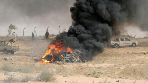 Forces loyal to Libya's UN-backed unity government gather at the site of a car-bomb attack carried out by an Islamic State (IS) group jihadist at the western entrance of Sirte on June 2, 2016. According to Libyan officials fighting resumed on June 1 on the outskirts of Sirte between their forces and jihadist during which three pro-government troops had been killed and 10 more wounded. Sirte was the hometown of slain dictator Moamer Kadhafi and, since seizing it in June last year, IS has turned it into a recruitment and training camp / AFP PHOTO / MAHMUD TURKIA