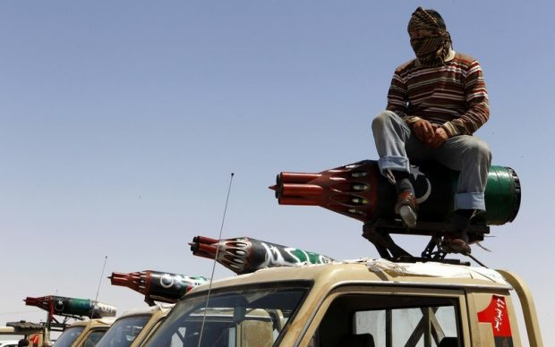 A rebel fighter sits atop pick-up trucks mounted with rocket launchers taken off helicopter gunships, at the frontline along the western entrance of Ajdabiyah April 13, 2011. Britain pressured other NATO members to beef up ground attacks in Libya on Wednesday as foreign ministers met in Qatar to try to open the deadlock in the country's civil war. REUTERS/Yannis Behrakis (LIBYA - Tags: POLITICS CIVIL UNREST CONFLICT TRANSPORT ODDLY IMAGES OF THE DAY)