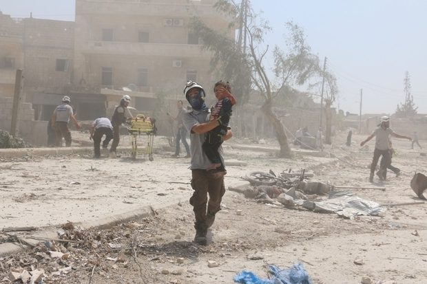 A Syrian rescue woker carries a child in the Maadi district of eastern Aleppo after government aircrafts reportedly dropped explosive-packed barrel bombs (AFP)