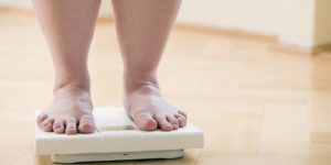 legs of overweight woman checking her weight on bathroom scales