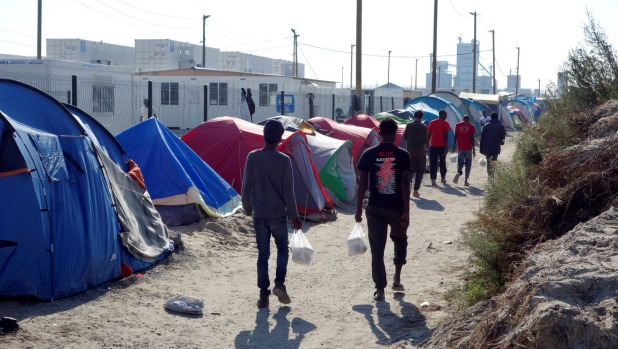 """Refugees walk in the northern area of the camp called the """"Jungle"""" in Calais, France. CHARLES PLATIAU/REUTERS"""