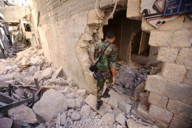 A Syrian soldier walks through the war-damaged al-Farafira souk in Aleppo's historic city centre on September 16, 2016 ©Youssef Karwashan (AFP)