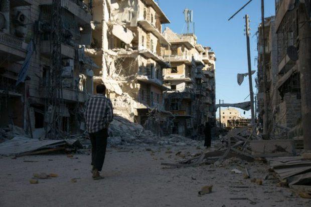 A Syrian man walks past a heavily damaged building following air strikes on rebel-held eastern areas of Aleppo ©Karam al-Masri (AFP)