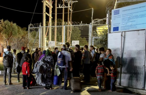 Refugees and migrants stand at the closed gate of the Moria migrant camp, after a fire at the facility, on the island of Lesbos, Greece, Sept. 19, 2016.