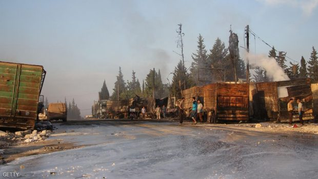 Syrians gather near damaged trucks carrying aid on the side of the road in the town of Orum al-Kubra on the western outskirts of the northern Syrian city of Aleppo on September 20, 2016, the morning after a convoy delivering aid was hit by a deadly air strike. The UN said at least 18 trucks in the 31-vehicle convoy were destroyed en route to deliver humanitarian assistance to the hard-to-reach town.  / AFP / Omar haj kadour        (Photo credit should read OMAR HAJ KADOUR/AFP/Getty Images)