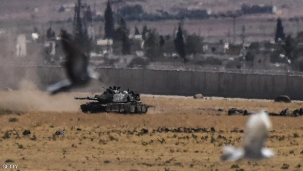 Birds fly near a Turkish tank coming from Syria during clashes between Turkish army and ISIS militants on September 4, 2016 at Elbeyli, in the southern region of Kilis. Ankara stepped up its fight against militants in Turkey and northern Syria with air strikes on Kurdish rebel positions in the restive southeast and IS extremists in northern Syria, security sources said on September 4, 2016.  / AFP / BULENT KILIC