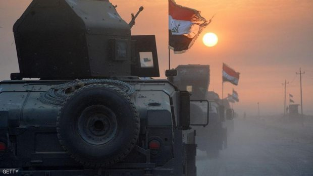 Pro-government forces drive in military vehicles in Iraq's eastern Salaheddin province, south of Hawijah, on October 10, 2016, as they clear the area in preparation for the push to retake the northern Iraqi city of Mosul, the last Islamic State (IS) group held city in Iraq.  / AFP / Mahmoud al-Samarrai