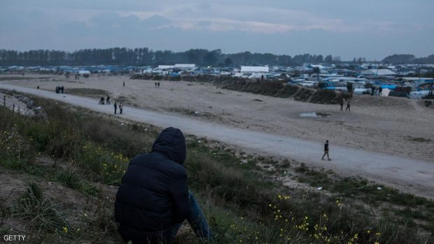 A Migrant sits in the Calais Jungle in Calais, France  on an embankment an looks in the direction if the camp on 23 October 2016. The refugee camp on the coast to the English Channel is to be cleared on monday, according to the French government. The approximately 8,000 refugees are distributed to various reception centers in France. (Photo by Markus Heine/NurPhoto via Getty Images)