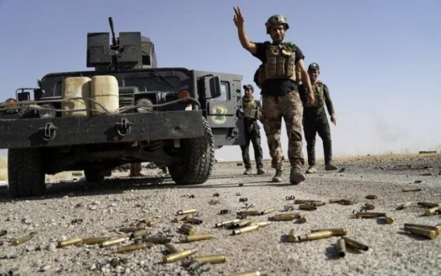 A member of Iraqi security forces gestures at Bartila in the east of Mosul during an attack on Isil in Mosul. REUTERS