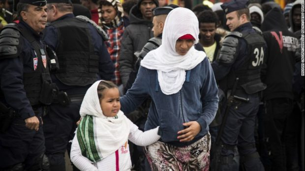 Refugees get ready to leave Calais as demolition begins at the Jungle migrant camp Tuesday