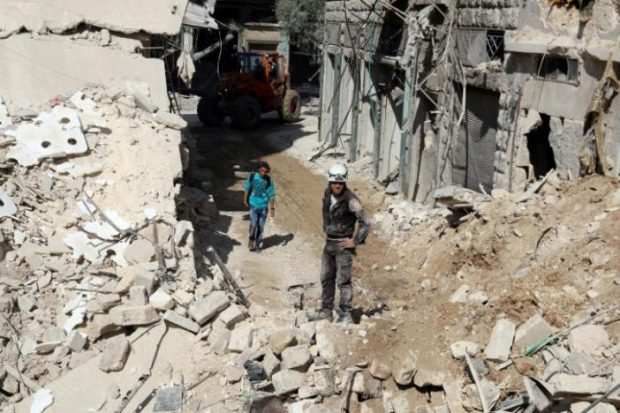Civil defence members and men inspect a site damaged after an airstrike in the besieged rebel-held al-Qaterji neighbourhood of Aleppo, Syria October 11, 2016. REUTERS/Abdalrhman Ismail