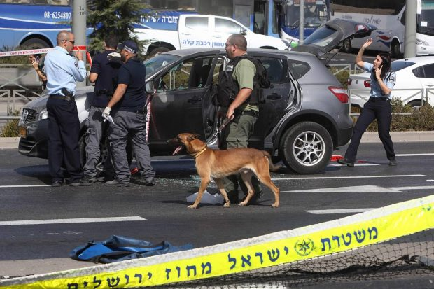 Israeli forensic policemen collect evidence from a car following a shooting attack in East Jerusalem on Sunday. PHOTO: AGENCE FRANCE-PRESSE/GETTY IMAGES