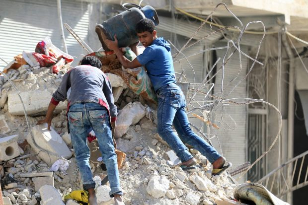People remove belongings from a site damaged in an airstrike in the rebel-held al-Qaterji neighborhood of Aleppo, Syria, on Oct. 17. PHOTO: REUTERS