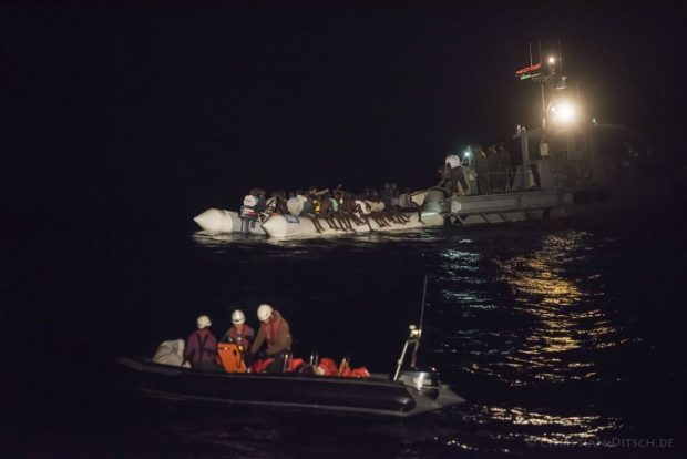 In this Oct. 21, 2016 picture provided by Sea-Watch aid group, refugees sit in a inflatable boat, background left, while a speedboat, labelled as Libyan Coast Guard, background right, and Sea-Watch members in a boat foreground arrive off the Libyan coast in the Mediterranean Sea. The German aid group Sea-Watch urged the European Union on Tuesday Oct. 25, 2016 to reconsider its plans to train Libyan forces to conduct sea rescue operations after a vessel labeled as belonging to the country's coast guard attacked the dinghy full of migrants last week. Dozens of people were feared dead in the incident. (Christian Ditsch/Sea-Watch via AP)