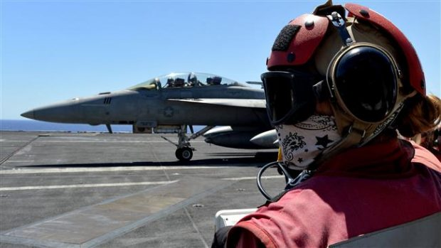 A picture taken on July 6, 2016 shows a sailor looking at an F/A-18F Super Hornet taxiing on the US Navy's super carrier USS Dwight D. Eisenhower, deployed in the Mediterranean in support of the US-led operations in Syria and Iraq. (Via AFP)