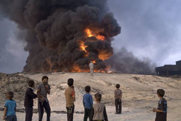 People watch a burning oil well in Qayyarah, about 31 miles (50 km) south of Mosul, Iraq, Sunday.   AP