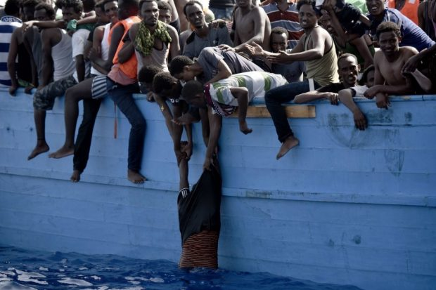 A migrant hangs from a boat drifting in the Mediterranean Sea about 12 nautical miles north of Libya on Oct. 4. (Aris Messinis/Agence France-Presse via Getty Images)