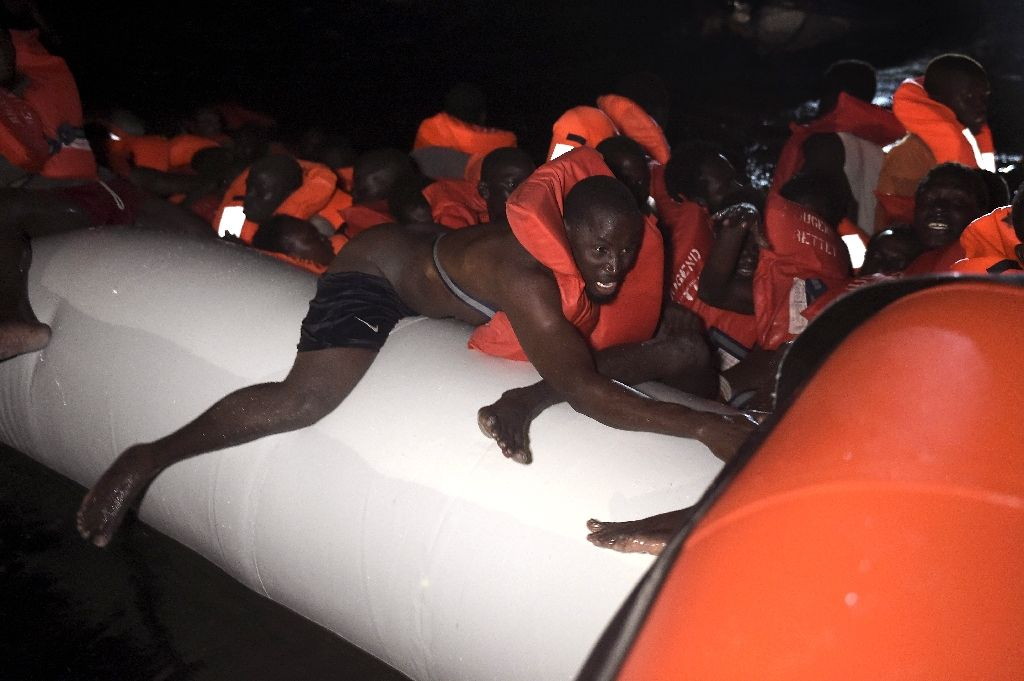 Refugees and migrant wait to be rescued as their rubber boat sinks some eight nautical miles off Libya's Mediterranean coastline (AFP Photo/Aris Messinis)